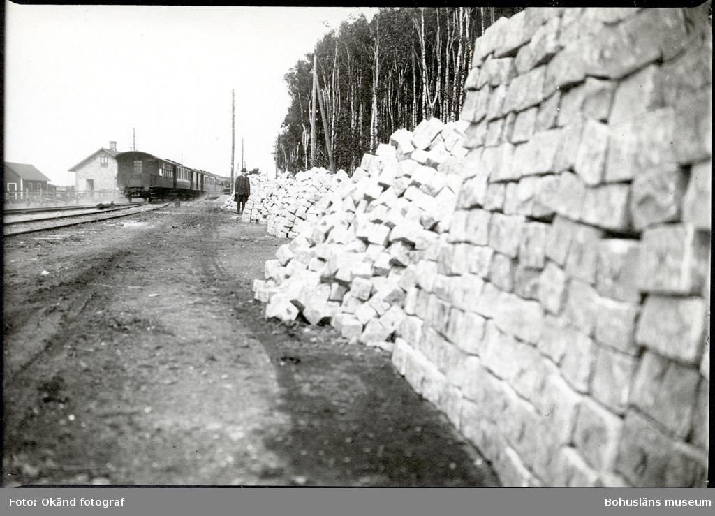 Upplag av gatsten längs en järnvägsräls, en man står i bakgrunden