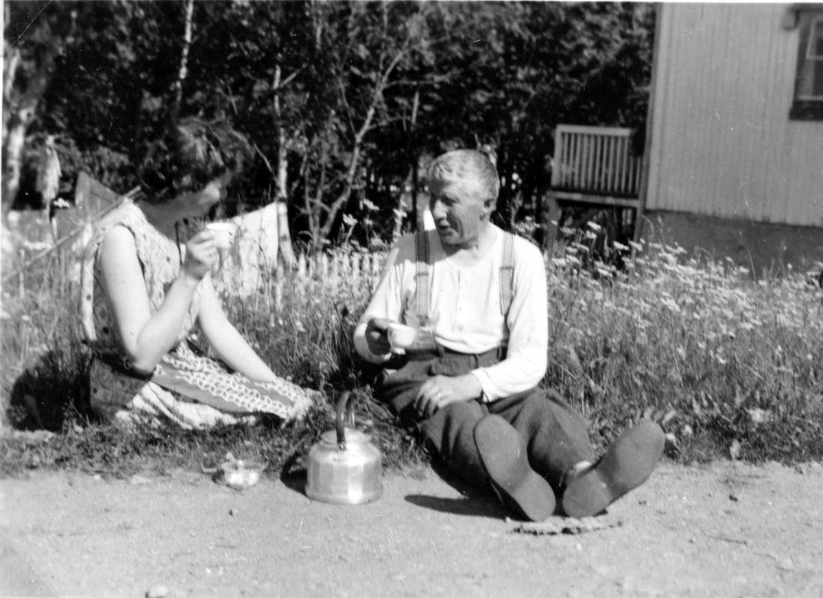 Kristian Elisar Rochmann og ei dame drikker kaffe ute. Stonglandseidet. Ca 1955.