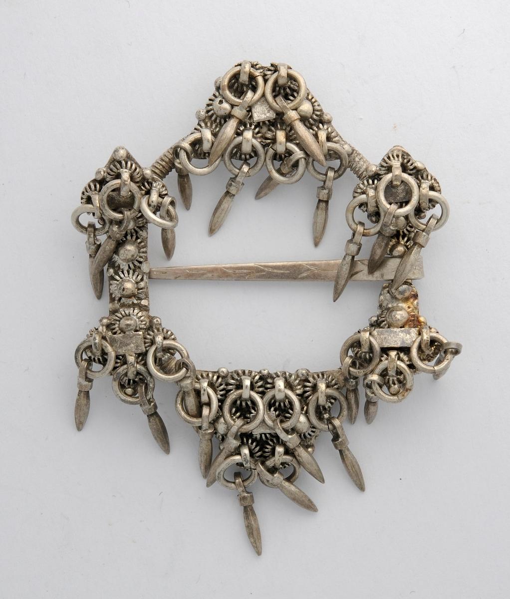 Sølje, hornring i sølv, ingen stempel. På baksida støypt ring med seks pålodda plater i ulike størrelsar. På framsida er platene dekorert med filigransarbeid og heng. Ei tann (nål) med lite dekor på.
