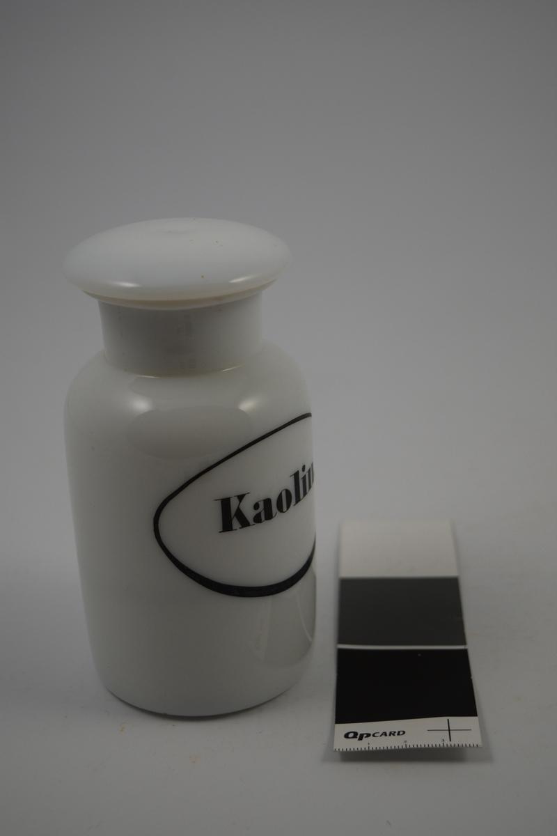 Hvit porselenskrukke med hvit propp. Påsatt etikett med sort oval ramme og sort skrift. Kaolin er syrenøytraliserende og ble brukt mot mageproblemer.