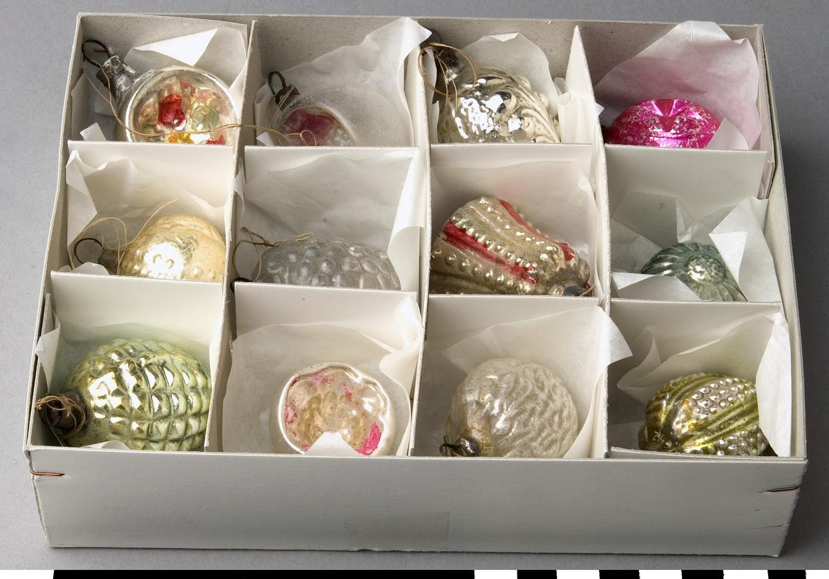 Julgransprydnad, 17 st, blåsta av glas i olika former; kulor, nötter, halvsfärer, o.s.v. med dekor i olika färger. Upphängning med bomullstråd i fjädrande ring med metalltråd. Storlekar från 38 till 53 mm.   Funktion: Dekoration i julgranen