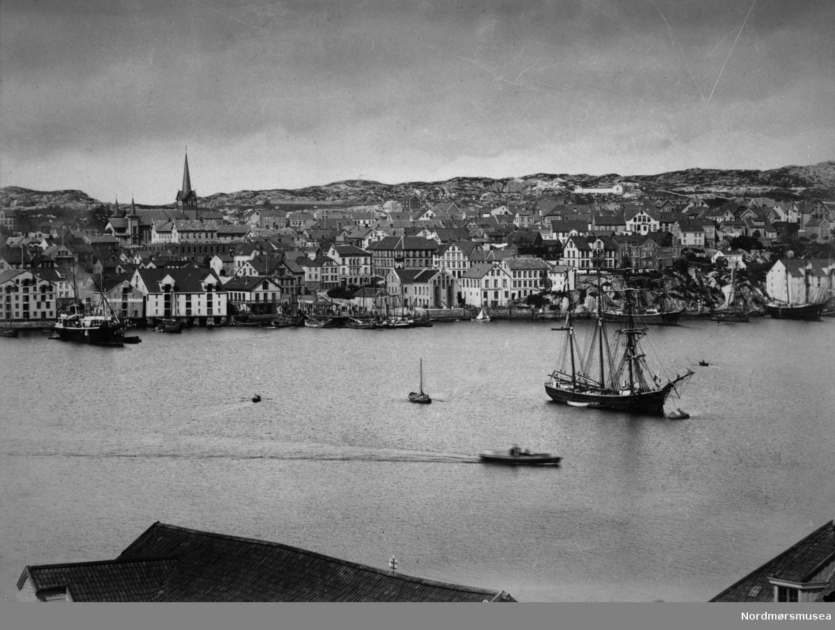 Fartøyet som ligger oppankret i forkant er en skonnertbark. Skipet til venstre har skorstein fra Bergenske Dampskipselskap.  Kirka, Piren, Blixhammeren. Kristiansund ca 1900. Nordmøre museums fotosamling.