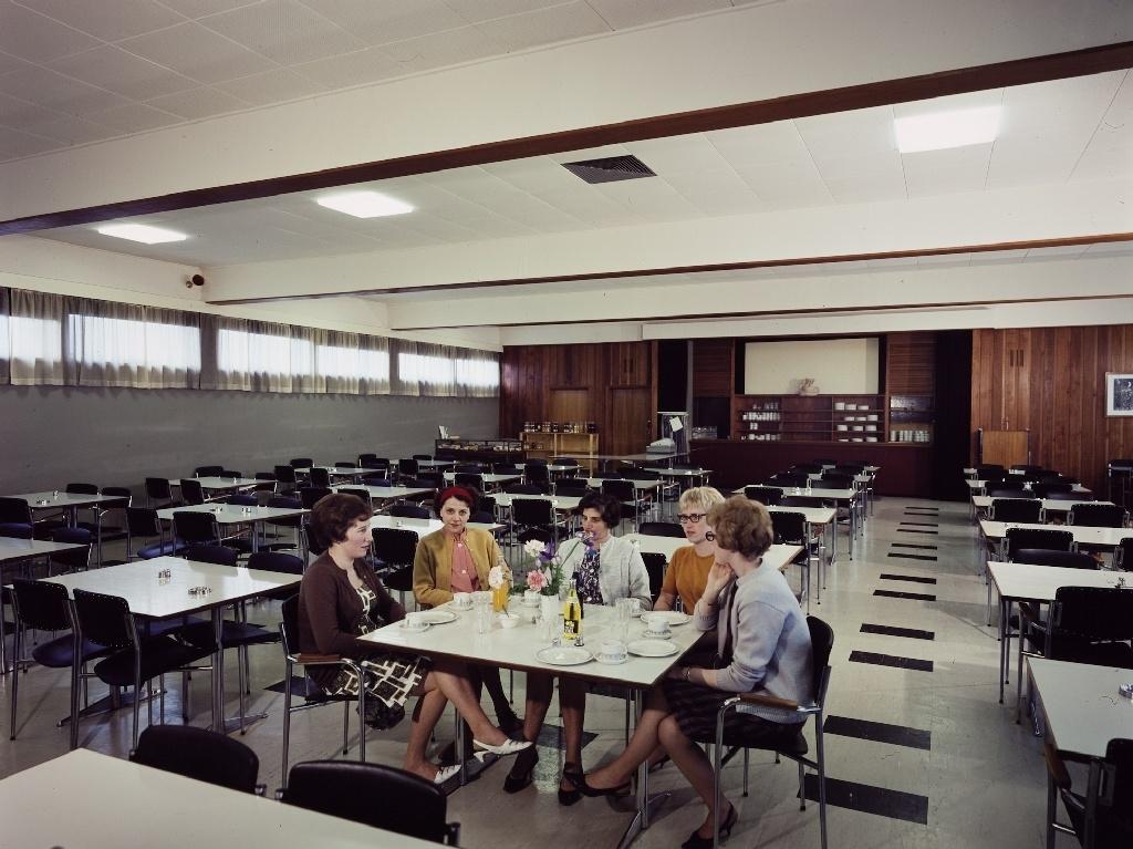 Fem kvinner sitter ved et bord i spisesalen til de ansatte i konfeksjonsfabrikken til Jonas Øglænd AS på Sandnes.