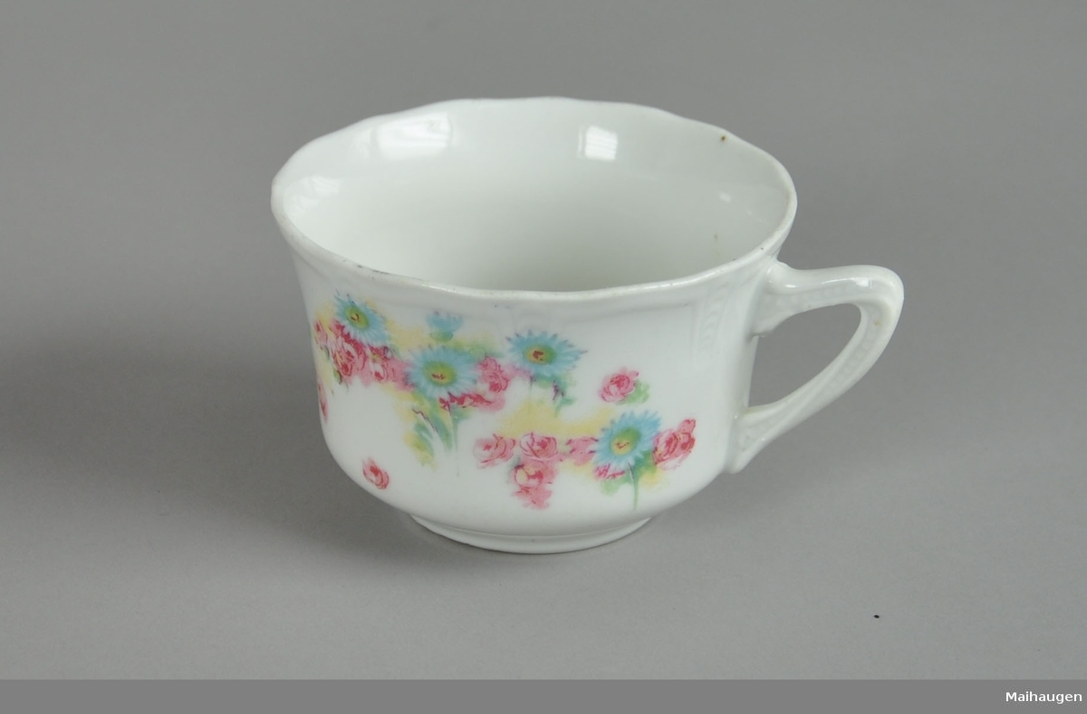 Kopp til servise, av glassert keramikk. På hanken og ved munneranden er det preget dekor. På koppen er det malt dekor med motiv av blomster.