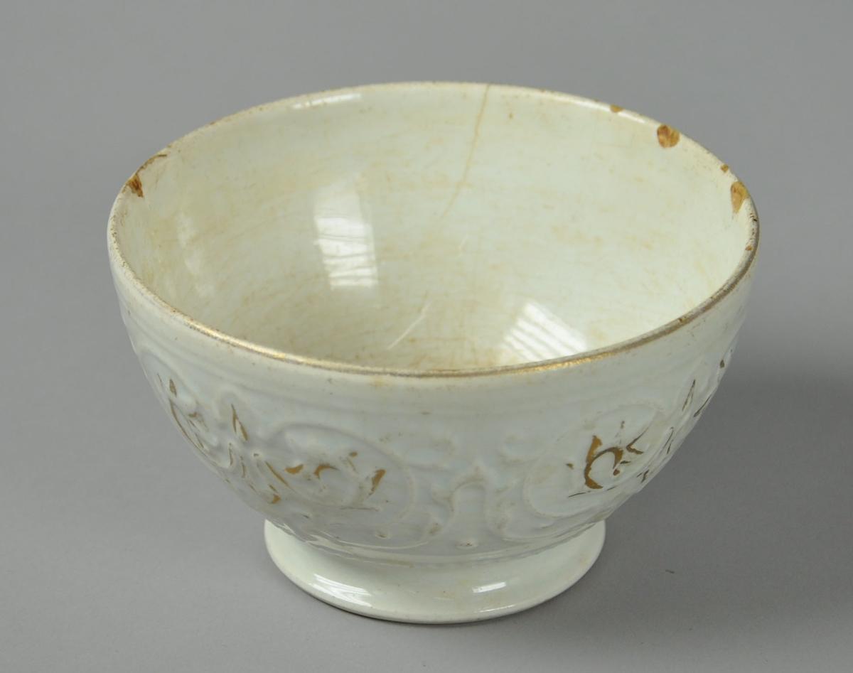 Hvit skål av glassert keramikk, med stett. Skålen har utstående dekor med spor av gullmaling.