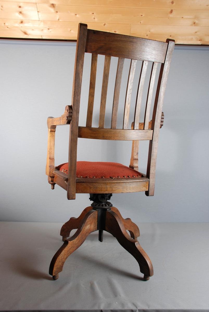 Svingbar armstol i tre med stoppet tekstilsete. Setet hviler på søylefot med fire skråstilte ben. Loddrette spiler i lett buet ryggbrett. Rettvinklede armlener festet til akterstolpe og sarg. Setet har rette sider og front, bak bueform, setet kan høydereguleres med er hjul på understellet.