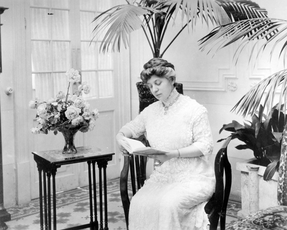Kvinne sittende ved bord og leser. Fru minister Michael Strøm Lie.