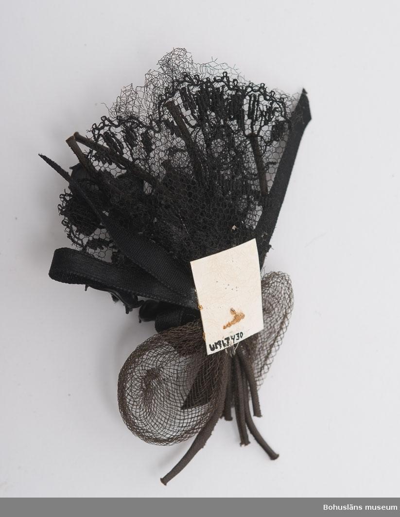 Bukett av svarta klockor av konstmaterial. Bakgrund av tyll och gles brun väv rosett av sammetsband. Har suttit på begravningskaramell.