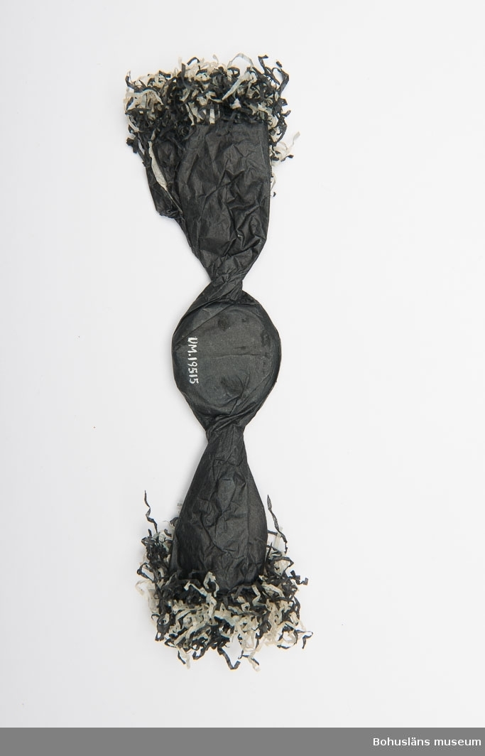 Begravningskaramell med svart och vitt silkepapper. Mitt på en duva i silverpapper fästad.  Se UM019490