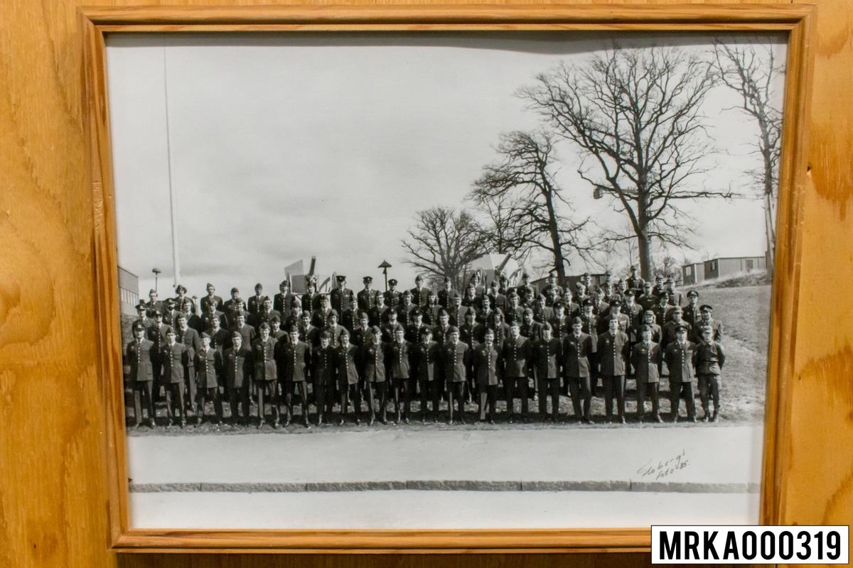 Fotografi taget på befäl och soldater som genomfört grundläggande soldatutbildning på 1:a Batteriet KA 2. Fotografiet taget vid vakten Rosenholm KA 2. Flobergs Foto 1985.