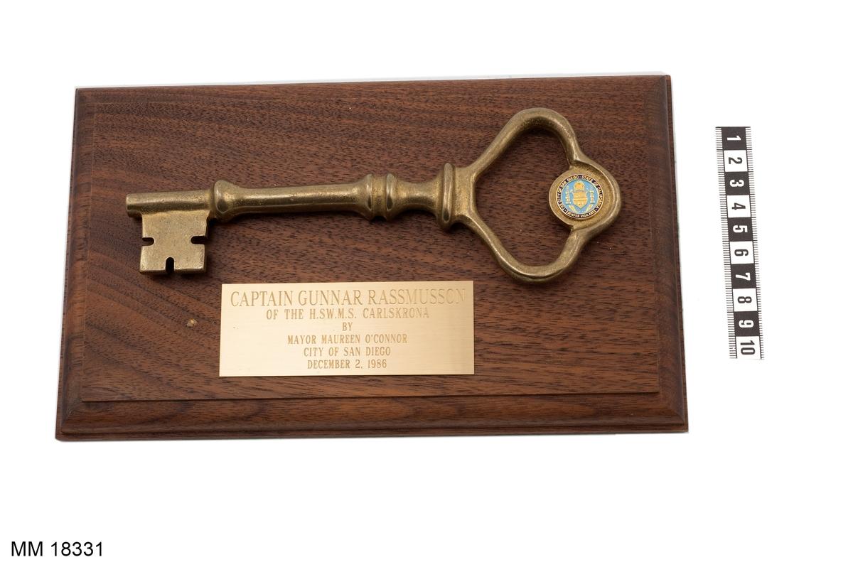"""Minnesplakett bestående av nyckel av mässing monterad på träplatta. På nyckeln sitter en litet emblem i guldfärg, ljusblått och mörkblått. Text runt kanten: """" THE CITY OF SAN DIEGO STATE OF CALIFORNIA SEMPER VIGILANS """". På träplattan mässingsplakett med ingraverad text: """" CAPTAIN GUNNAR RASMUSSON OF THE H.SW.M.S. CARLSKRONA BY MAYOR MAUREEN O´CONNOR CITY OF SAN DIEGO DECEMBER 2.1986 """". Baksida klädd med grön filt"""