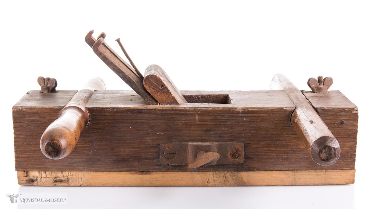 Rektangulær okshøvel med jern og kile. Jernet kan reguleres med skrumekanisme. Et dreid og et skåret håndtak er felt ned i avrundede spor foran og bak. Spor for høvling av fjær i sålen og regulerbare styringslister på hver side av sporet.