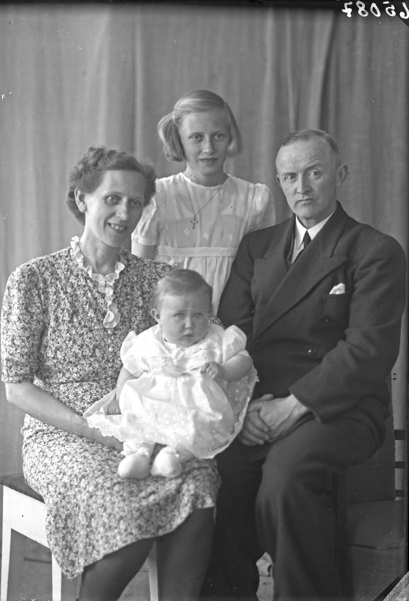 Gruppebilde. Familiegruppe på fire. Mor, far, en ung pike og et spebarn. Bestilt av John Olsen. Olav Kurresgt. 13.