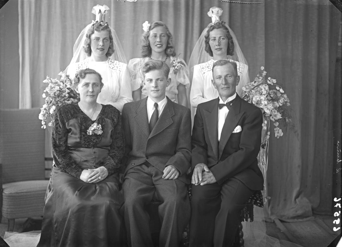 Gruppebilde. Familiegruppe på seks. To bruder, søstre, kvinne, mann og ung mann Bestilt av Einar Svanberg, Ole Ingvald Nøkling, Herr Kolstø.