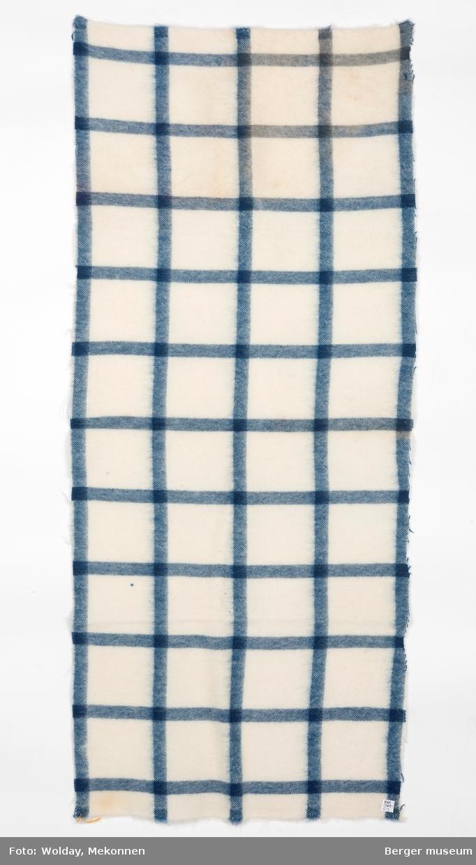 En pleddprøve i rutemønster. Prøven har klippede langsider, jarekant på kortsidene.  Mønsteret karakterisereres av blå striper i kvadratisk rutemønster på hvit bunn.