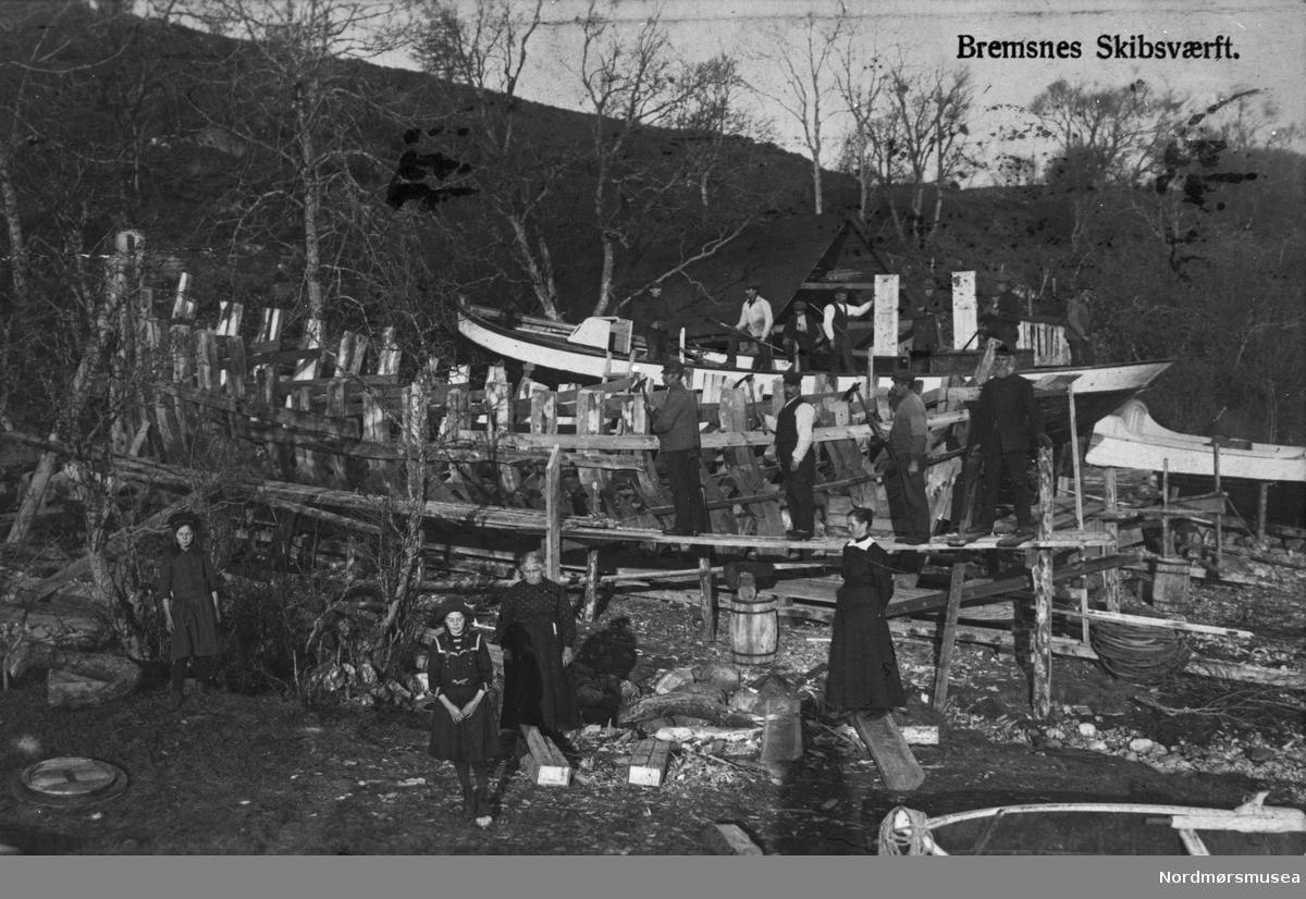 Bremsnes skipsverft, Averøy. Både den ferdige båten i bakgrunnen og den under arbeid i forgrunnen er kuttere.  Skipsbyggere med damer, familie, koner, døtre, arbeidsfolk, tømrere. Fartøy, Dalen? Ca 1890? Nordmøre museums fotosamling.