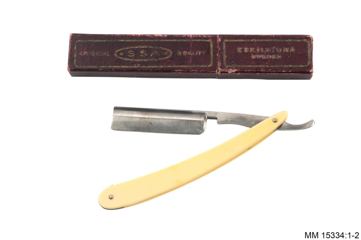 Avlång, gul-vit hylsa med två metallfästen, varav den ena bildar led till kniven. Kniven har bred rygg, yx-liknande form. På kniven står: Genco Safege och Geneva N.Y. USA