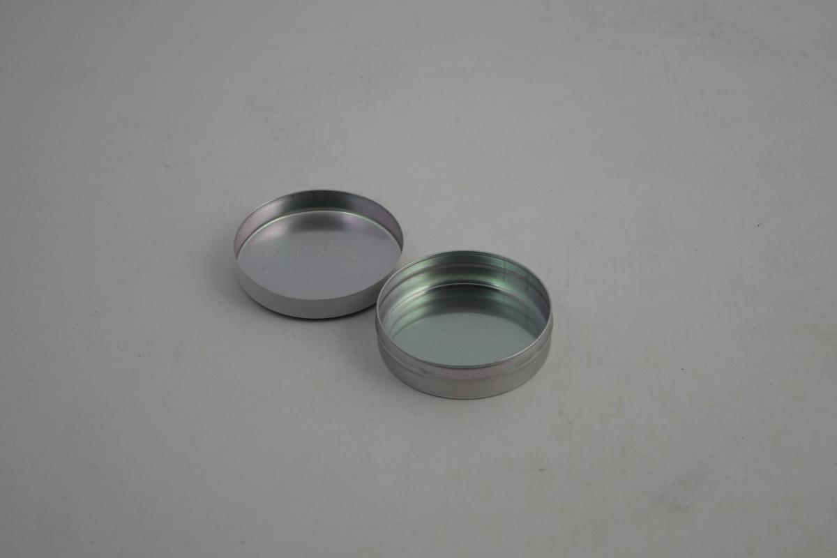 Salveeske i metall, aluminium, med hvitmalt lokk med skrift. Form: Sirkelformet med lokk