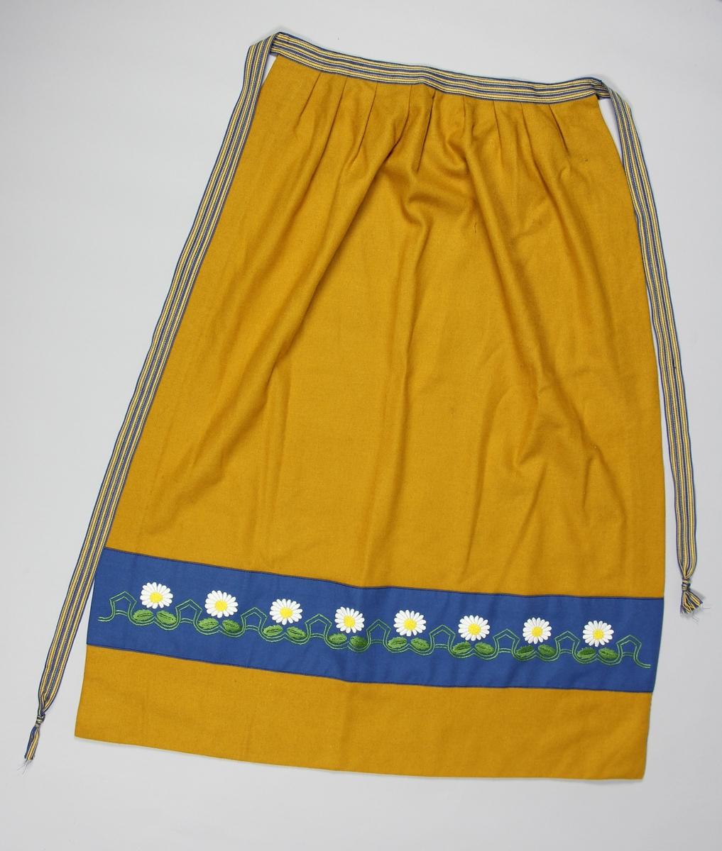 Förkläde till Sverigedräkten av gul tuskaftsvävt ylle. Veckat mot knytband ihopsytt av tre vävda blågula bomullsband. 10 cm upp från förklädets nedre fåll sitter en bård av blå ylle, 11 cm bred. Bården är broderad med vita prästkragar och en girlang av gröna slingor och blad.