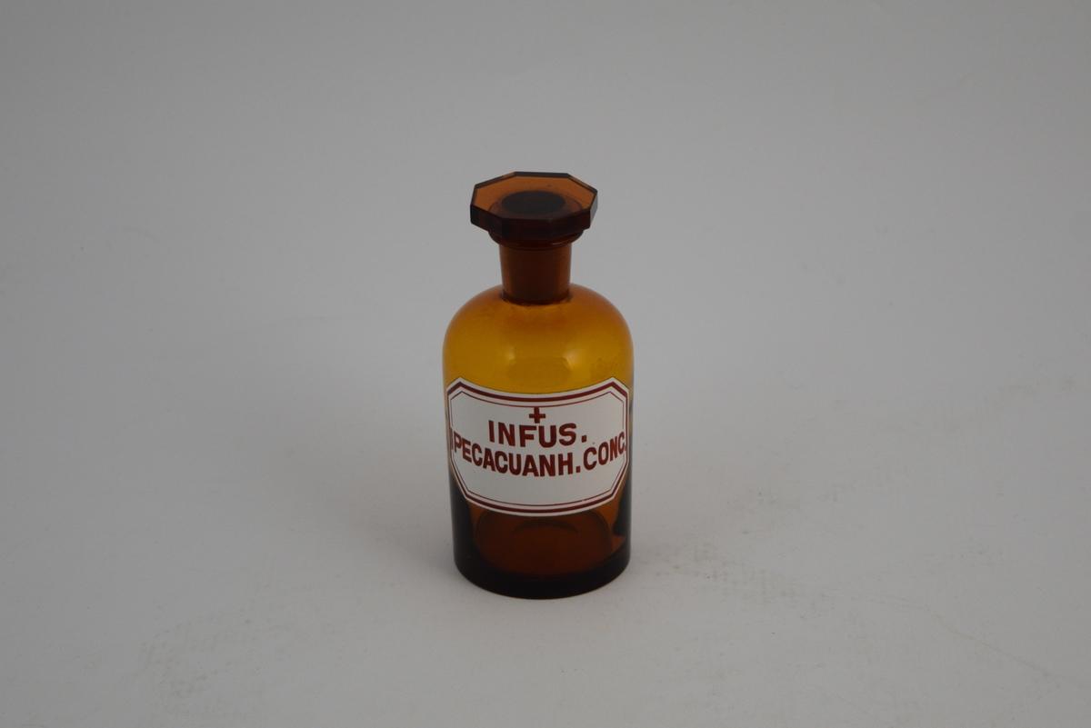 Brun glassflaske, smal hals, åttekantet glasspropp, slipt. Påsatt hvit etikett med rød skrift og et rødt kors, noe som indikerer at innholdet er giftig. Krukken har inneholdt Ipecacuanha infus. (Brekkrot-infus).