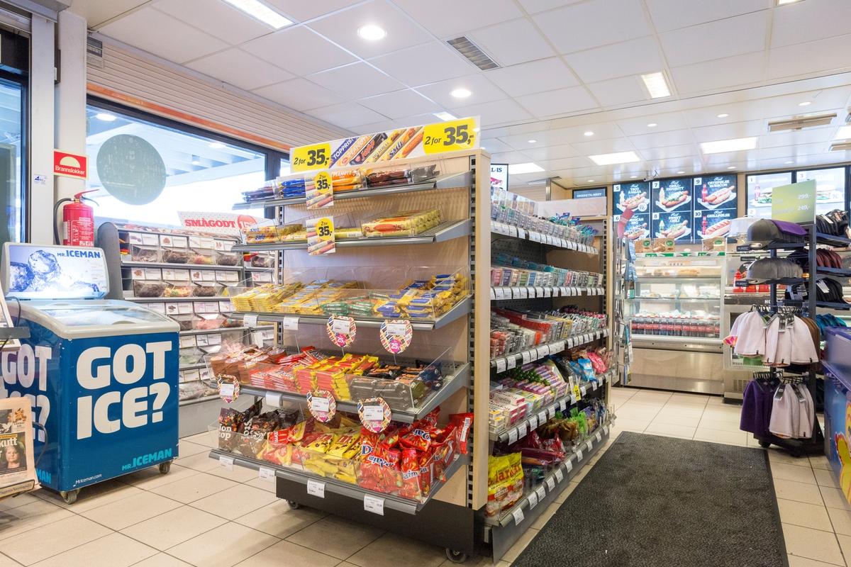 Statoil Nadderud. Butikk interiør med hylleseksjon med sjokolader og godteri. Isdisk. Butikkdisk i bakgrunnen.