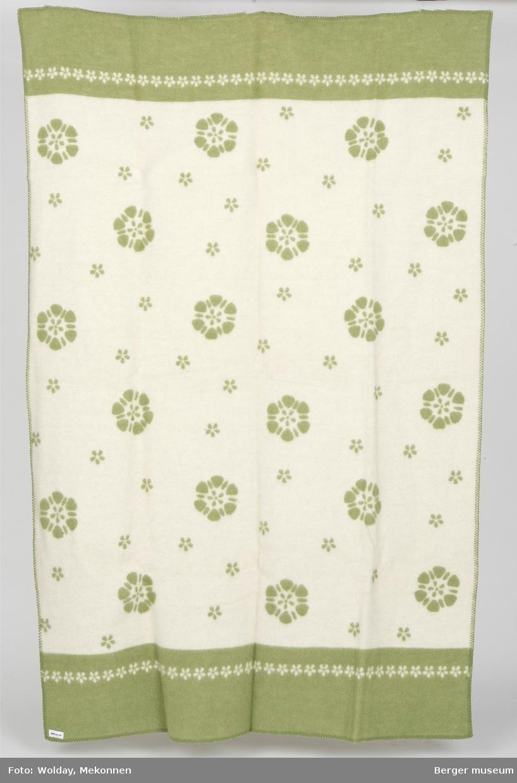 Enkle stiliserte blomster i ulike størrelser i hovedmønster. Små blomster på rekke i hvit bord.