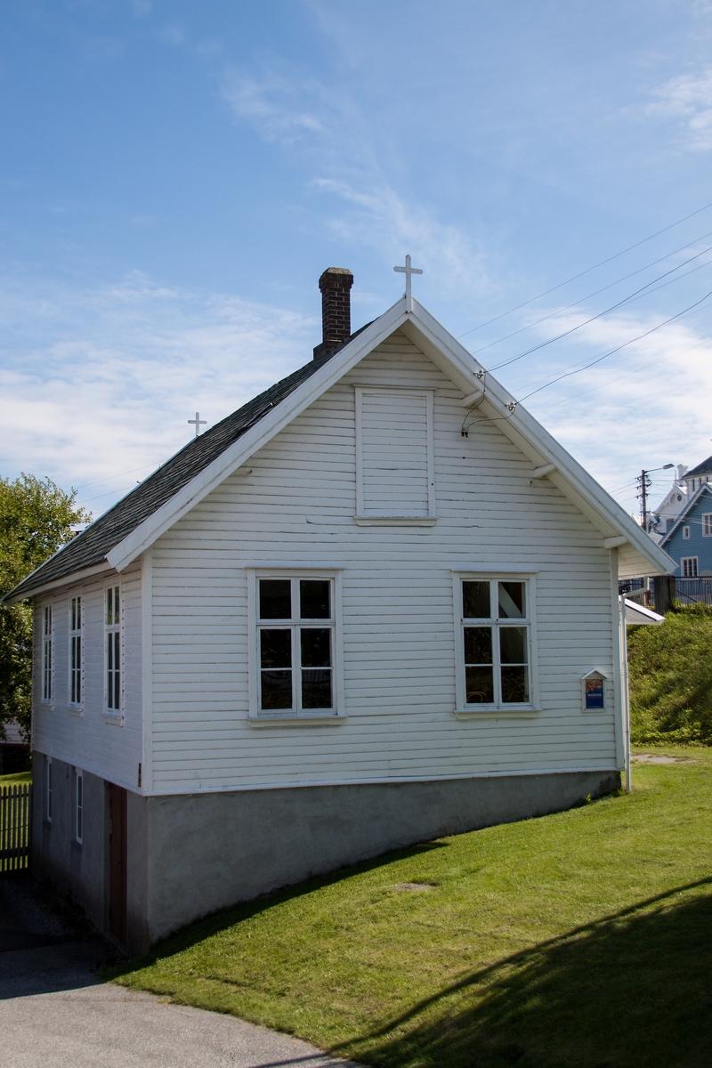 """Bedehuset er bygget i 1904. I 90 år sto det på sin opprinnelige tomt nord for """"De fem dårlige jomfruer"""" og Karmøybroen. Plasseringen i forhold til terrengets helling og adkomstvei var omtrent som nå. Huset er i prinsippet tatt vare på slik det var da museet overtok det i 1982. Allerede kort etter oppførelsen fikk huset direkte inngang fra bislaget til kammerset bak salen. Kjøkkenet ble forbedret. Det fikk takvinduer i stedet for vinduet i gavlen. Det opprinnelige pannetaket ble erstattet med skifer. El. Anlegg har huset hatt siden 1920.  Utvendig har huset alltid vært hvitt. Innvendig var det kort etter oppførelsen umalt. Senere var veggene rosa, taket hvitt og dørene grå. Nåværende fargeskjema skriver seg fra emissær og maler Andreas Kallesteins oppussing i 1950. Enkelte ådrete dørblad står urestaurert fra hans tid. Både kulørene og bruk av lasér-teknikker er karakteristiske for smaken her i distriktet på dette tidspunktet.   Etter 1960 fikk huset oljekamin, nytt, større bislag med tørrklosett i stedet for tidligere uthus, og  platelagt gulv med belegg til erstatning for det tidligere malte tregulvet. Bislaget, ovner og skorsteinssystem ble restaurert etter flyttingen til Dokken og har i dag opprinnelig utforming."""