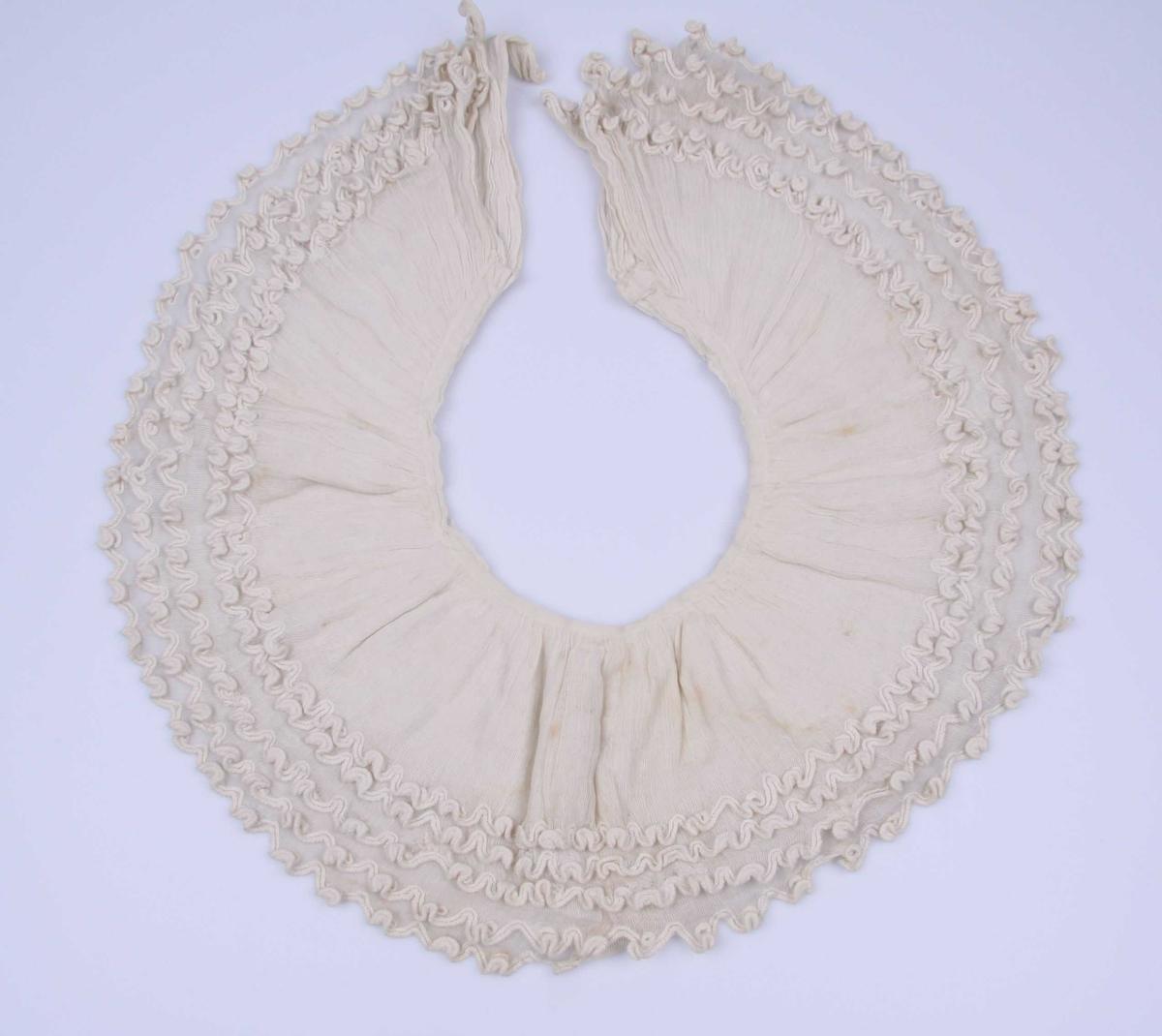 Av hvitt, meget åpent bomullsstoff. Kragen består av fem knapper avsluttet med dype tunger i tambur-søm og med brodert hull i hver tunge. Tett rynket ved halsen med kant av stoffet.