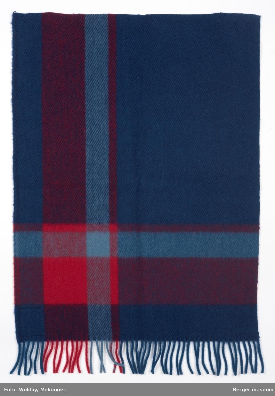 Rutevevd pledd i blå og røde nyanser. Teppet er klippet til ca. 1/4. Rutemønster i hjørne, med et større blått felt på midtpartiet. Frynser på ene kortsiden.