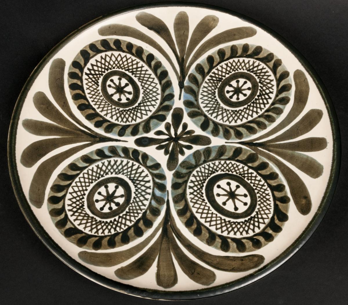 """Fat av förmodligen stengods, formgivet av Berit Ternell för Gefle Porslinsfabrik, modell -T56. Runt, skålformat med två fotringar. Handmålad originaldekor av Ternell, """"Fyra rundlar"""". Fyra ovaler med mönster i och omkring, olivgröna nyanser mot beige glasyrfond. Signerad under med olivgrönt """"BT -62 11-4"""" samt otydlig blå stämpel med text."""