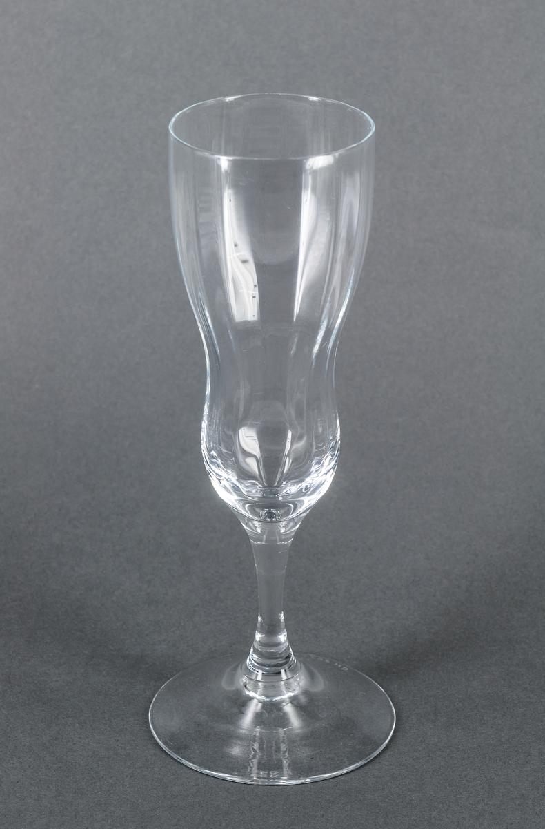 Champagneglas, prov, ofärgat. Hög, smal kupa med optik, överst konvex övergående i konkavt parti. Rundat, konkavt ben. Design Gunnar Cyrén för Orrefors Glasbruk.