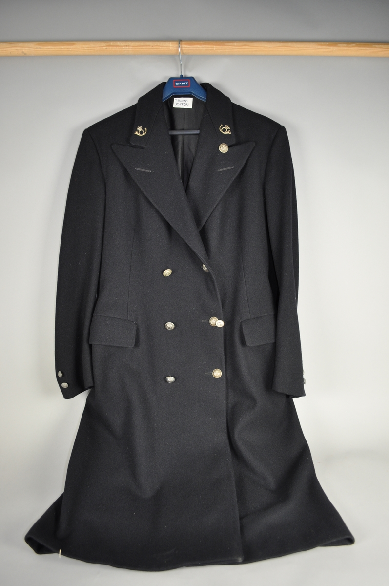 Mørkeblå uniformsfrakk.  Påsydd sølvfargede posthorn.