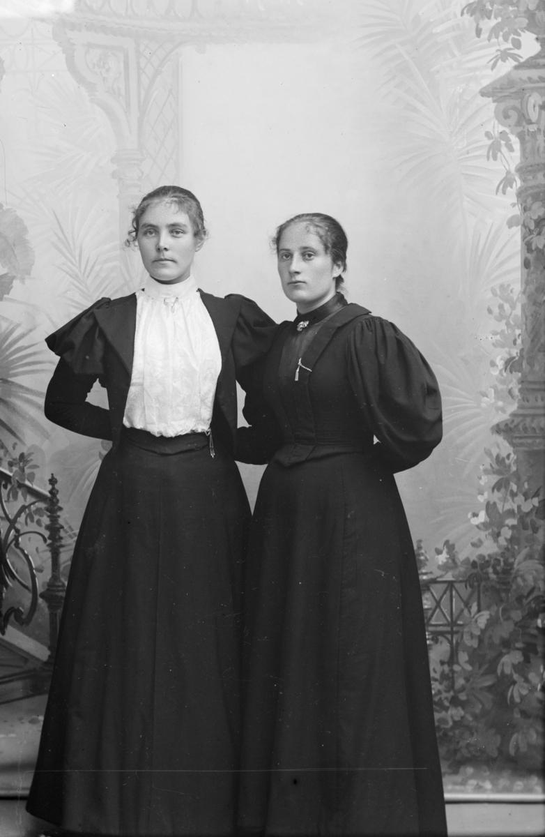 Portrett, to kvinner står ved kulisse, helfigur. Karen Stormyhren til høyre.