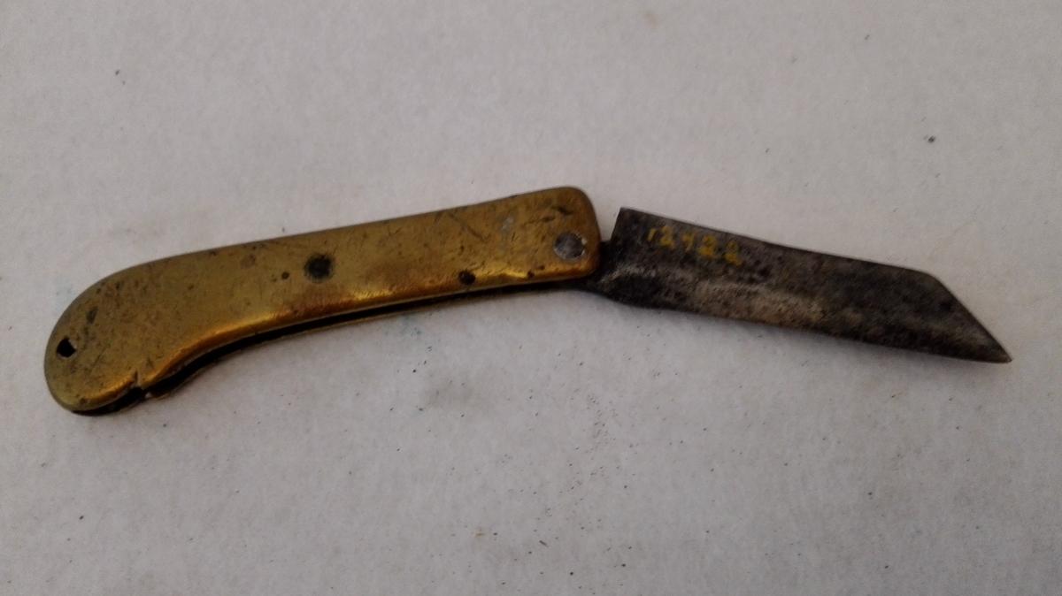 2 foldekniver med messsingskaft (12421 - 22)  To foldekniver med messingskaft. Skaftene er av samme type og helstöpne med fure paa den ene side for kniven sammenfoldet. Kniverne er av grovt hjemmearbeide, den ene med avrundet egg endende i en spiss foran, den anden med ret egg og spiss nedslipt fra ryggen. Skaftenes længde ca 9,5 cm.  Kjöpt av Anfin Bakke, Kirkevold, Borgund.