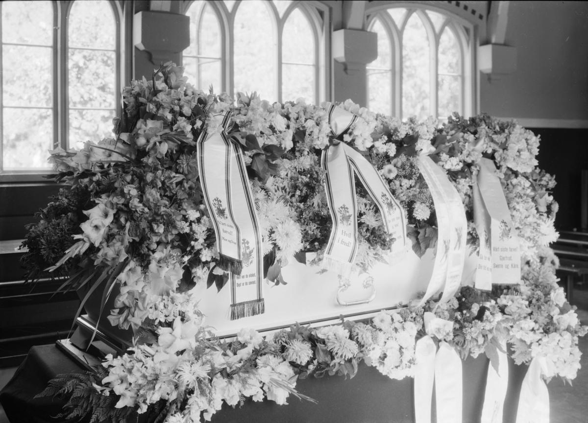 Begravelse fra Lillehammer kapell. Blomsterdekket kiste med sløyfer.