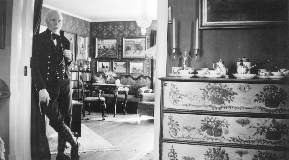 Interiør fra stue med mange malerier og en person - antakelig Alf Lundeby