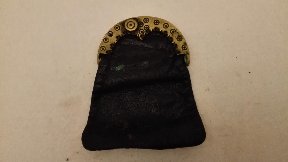 1 pung med pungelås  Skindpung med pungelås av messing, 7,3 cm bredt, forsirt med indstemplete prikker med ring omkring.  Gave fra gårdbruker A.B. Sörestrand, Lavik.