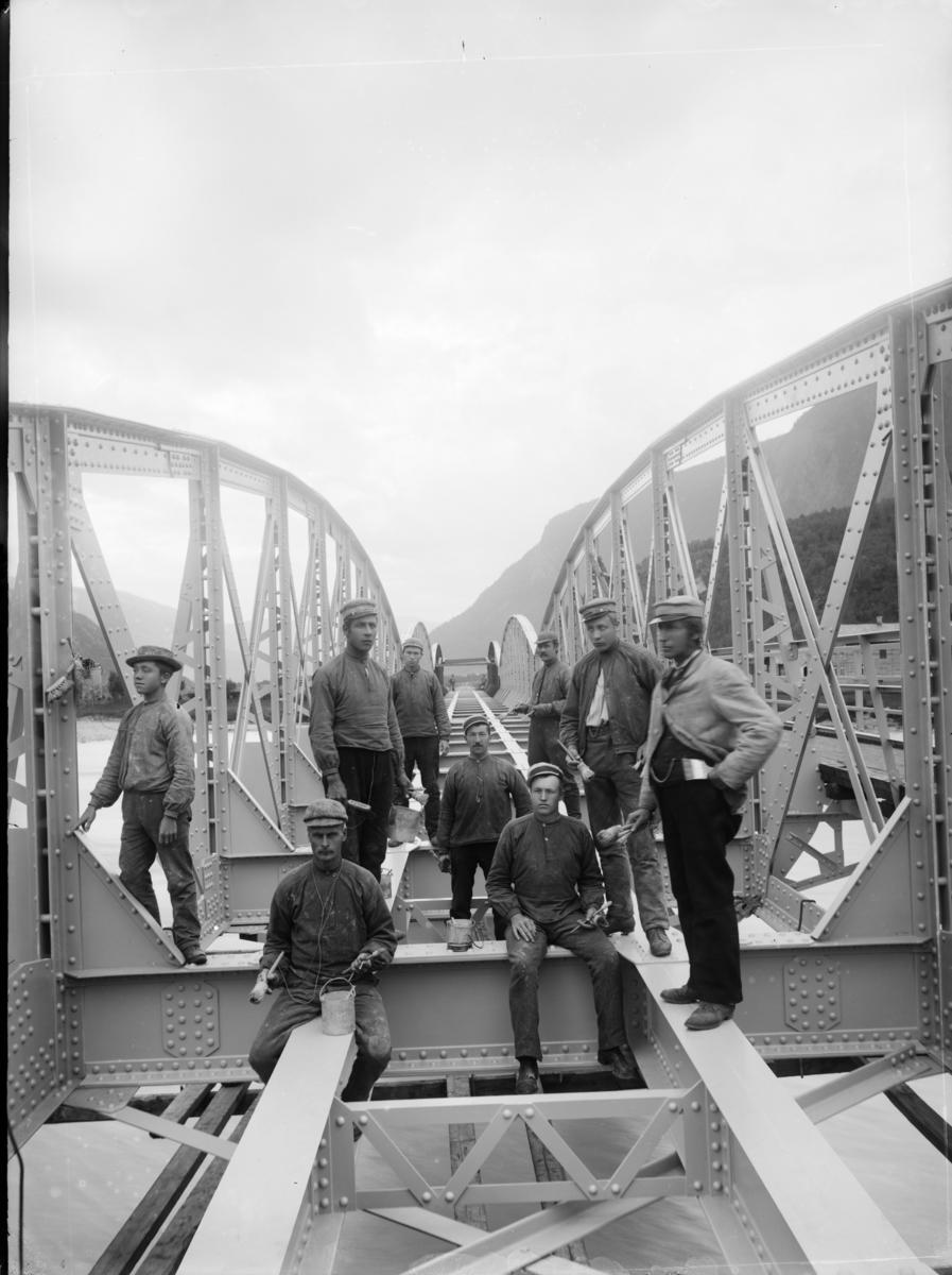 Jernbanebru,fagverksbru i stål,  over Otta elv ved Otta under bygging. Malingsarbeider utføres av 9 mann.