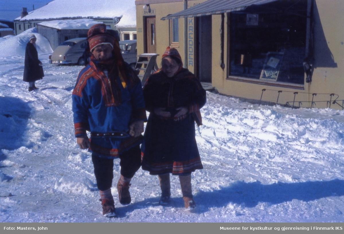 Honningsvåg. En samisk dame og en samisk mann i kofte. I bakgrunnen skredderbutikken. 1962/63.