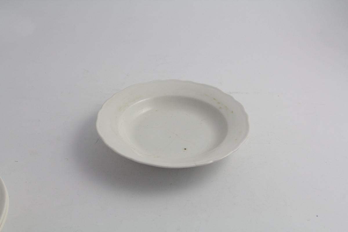 Rund, dyp tallerken. Hvit farge, bølgekant på fane.