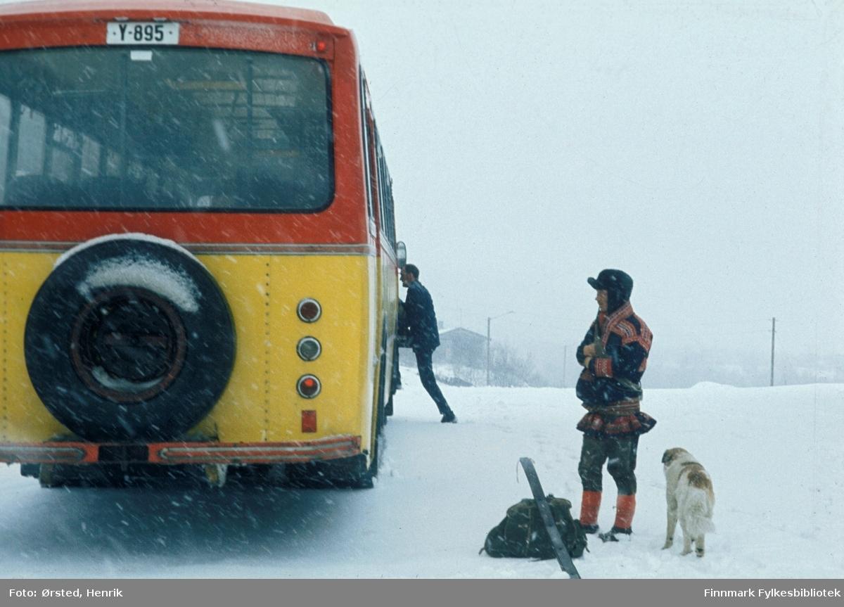 Rutebussen utenfor butikken i Masi (Máze på samisk) på 1970-tallet. Det er vinter og bussen tar med seg posten innsamlet av postfører Mathis Mathisen Buljo og bringer den videre. En passasjer i kofte, med ryggsekk, ski og trekkhund står utenfor bussen (Se også FBib.10001-285).  Bussen er registrert Y-895. Det var en Volvo B57, karosseri bygd hos Vestfold Bil og Karosseri (VBK), Horten, 1969-modell. Eier av bussen var Finnmark Fylkesrederi og Ruteselskap (FFR) og den er lakkert i selskapets karakteristiske farger, skarp gul og rød.   Fotograf Henrik Ørsteds bilder er tatt langs den 30 mil lange postruta som strakk seg fra Mieronjavre poståpneri til Náhpolsáiva, videre til Bavtajohka, innover til øvre Anárjohka nasjonalpark som grenser til Finland – og ruta dekket nærmere 30 reindriftsenheter. Ørsted fulgte «Post-Mathis», Mathis Mathisen Buljo som dekket et imponerende område med omtrent 30.000 dyr og reingjetere som stadig var ute i terrenget og i forflytning. Dette var landets lengste postrute og postlevering under krevende vær- og føreforhold var beregnet til 2 dager. Bildene gir et unikt innblikk i samisk reindriftskultur på 1970-tallet. Fotograf Henrik Ørsted har donert ca. 1800 negativer og lysbilder til Finnmark Fylkesbibliotek i 2010.