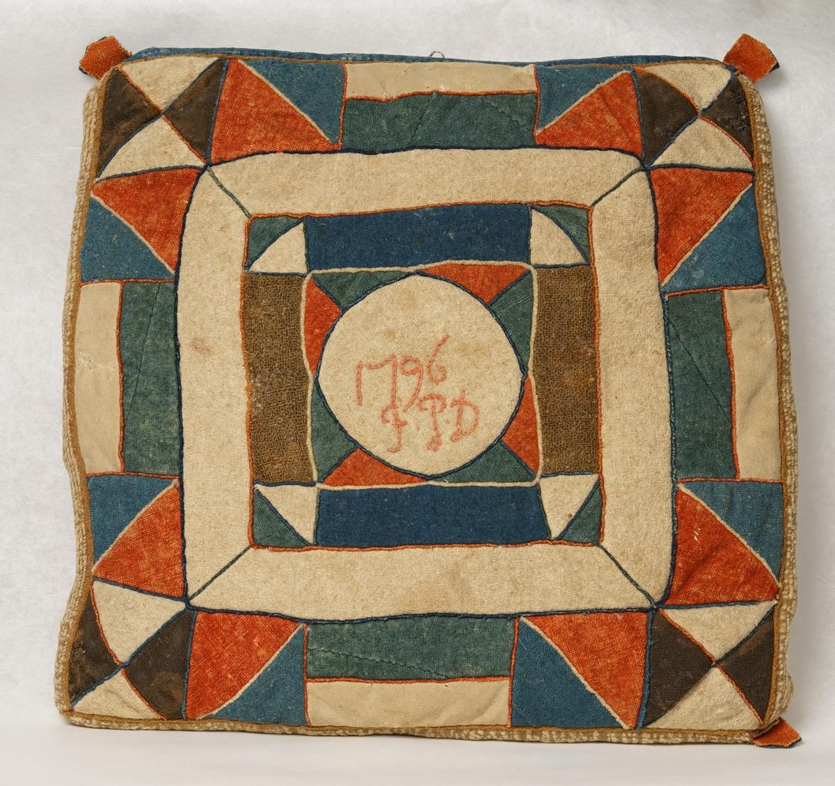 Skarvsömsdyna med framsida av yllelappar i flera olika färger: rött, blått, grönt, vitt och brunt. Kudden är märkt med broderi i mitten 1796 F.P.D . Baksidan är av linnelärft, sekundärt.