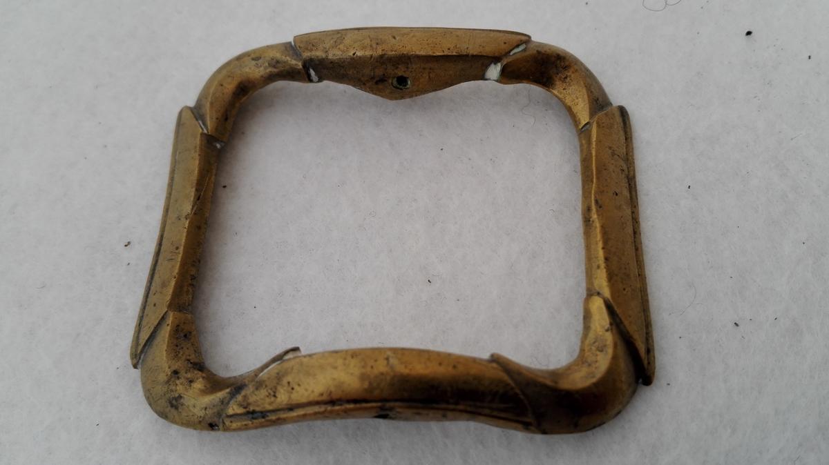 2 par messing skospænder (11708 - 09).  To par messing skospænder av vanlig type. Stöpte. Tand av jern, mangler paa en spænde.  Det ene par er 5,5 cm langt, det andet 6 cm.  Kjöpt paa auktion efter Ingebrigt Kvammen, Hagen, Kaupanger.
