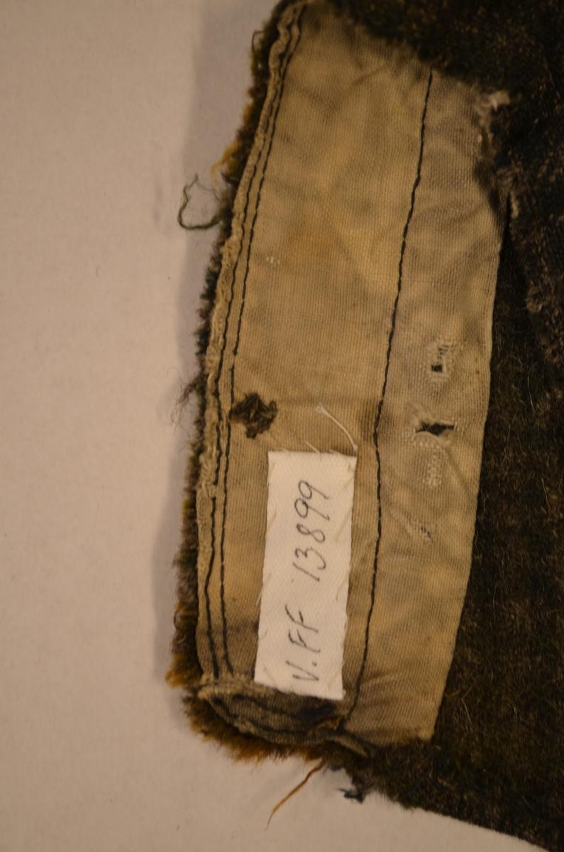 Bukse til gutt i småruta ulltøy, Lappa framme med eit stort stykke brunt ulltøy. På eine kneet endå ein ny lapp utanpå. Stor lapp i baken også.  Gylf med to knappar og knappehol. Linning med knapp og knappehol. Opning midt bak med ein splitt 5,5 cm. Lomme i kvar side. Hol ved eine lomma.