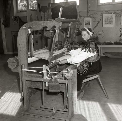 FIB-fotografi från utställning i Färila. Kvinna iklädd hembygdsdräkt sitter vid den gamla vävstolen 9 juli 1958.
