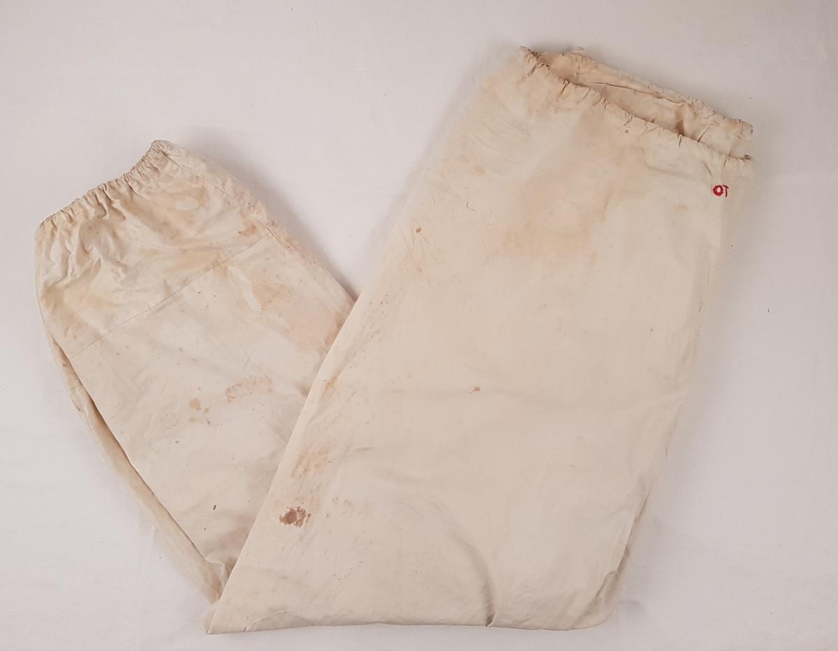 """Hvit bukse med strikk i livet og ankellinningen. På fremsiden av buksen er det brodert """"OT"""" med rød tråd."""