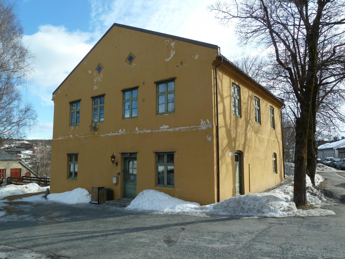 Murbyggning i to etasjer med loft og kjeller. Pusset og gulmalt. Teglsteinstak.