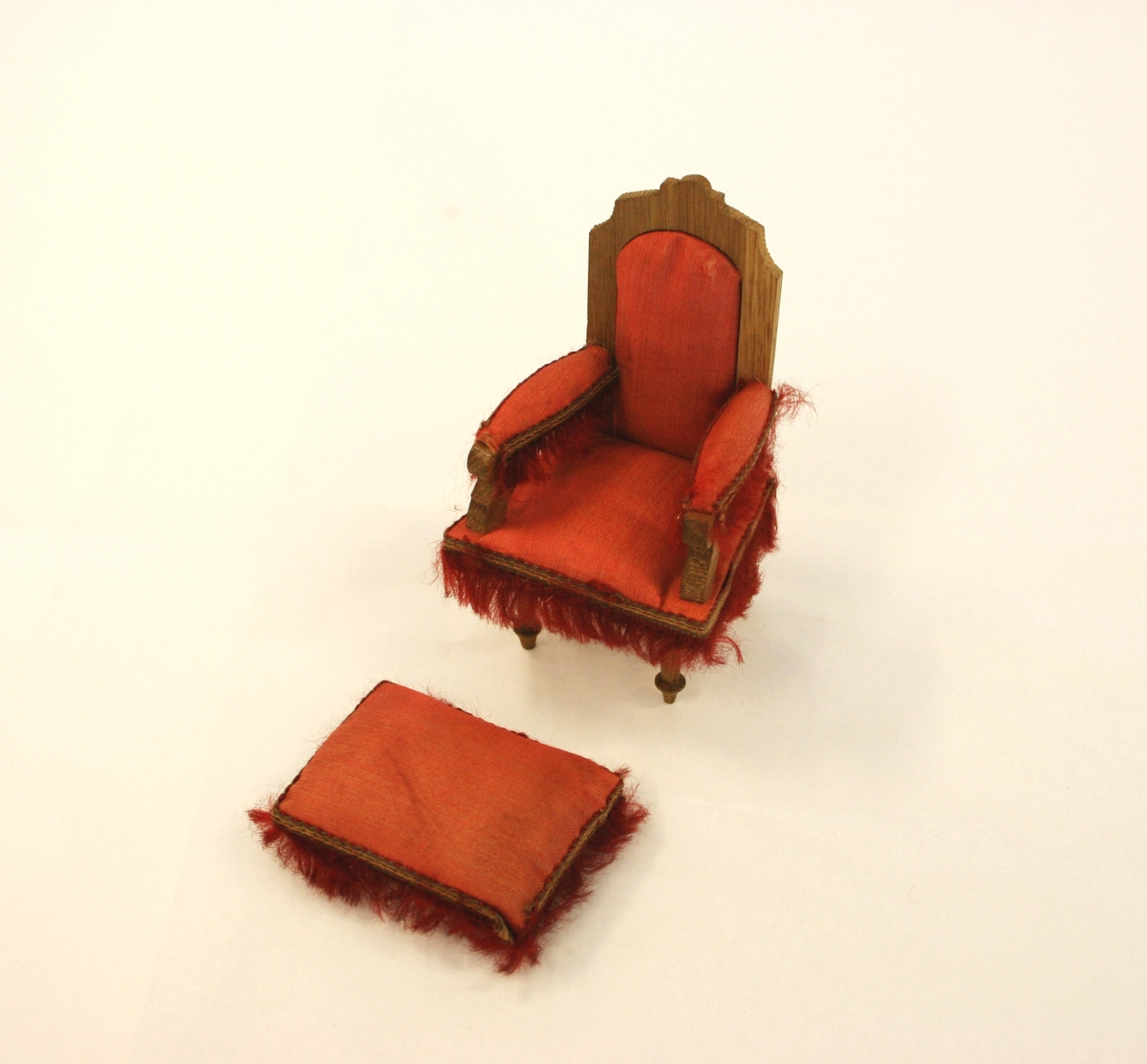 Dukkemøblement 9 deler:  A) Sofa i rødt silke på setet, rygg og armlener (lener med pøller). Høy rygg med utskjært toppgavl i tre. Røde frynser nederst i fronten, på sidene og røde dusker på pøllene.  B) Lenestol med frynser i front på sidene og på armlenene. Høy rygg med rødt silke på setet, ryggen og armlener.  C) Stol med rødt silke på setet og røde frynser rundt stolsetet. Dreide forben, høy, svunget rygg med løvsagarbeid. D) Bord i tre med avrunede sider, fire freide ben hvorav et ben er surret øverst i hvit bandasje.  E) Konsollspeil med marmorplate og gavl med trespir med fire lave kuleføtter. Speil med utskjært treramme. Dreide ben fra marmorplaten ned til understellet. F) Fotkrakk i rødt silke med røde frynser rundt hele. Nederst er fire lave kuleøftter.