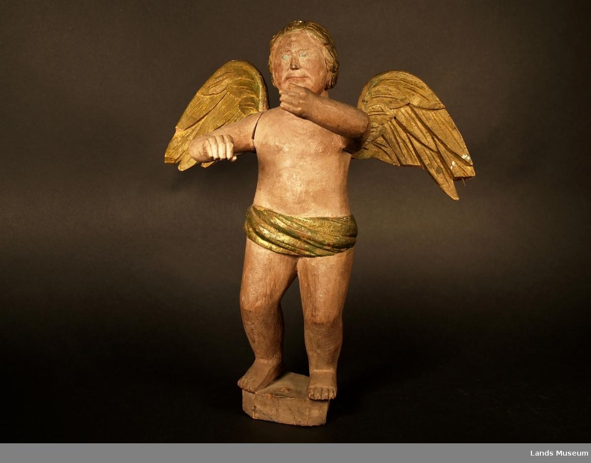 Trefigur, engel med forfylte vinger, hår og lendeklede som er drapert. Står på en trekloss. Engelen har fremstrakte armer.