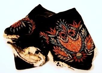 Ett par kyrkvantar av svart sammet, fodrade med renskinn. Vantarna har broderier med silkegarn utfört i plattsöm och stjälkstygn i färgerna blått, vitt och rött. Öppningar både på vantarnas- och tummarnas baksida är kantade med vitt skinn. Öppningarna är till för att kunna bläddra i psalmboken.